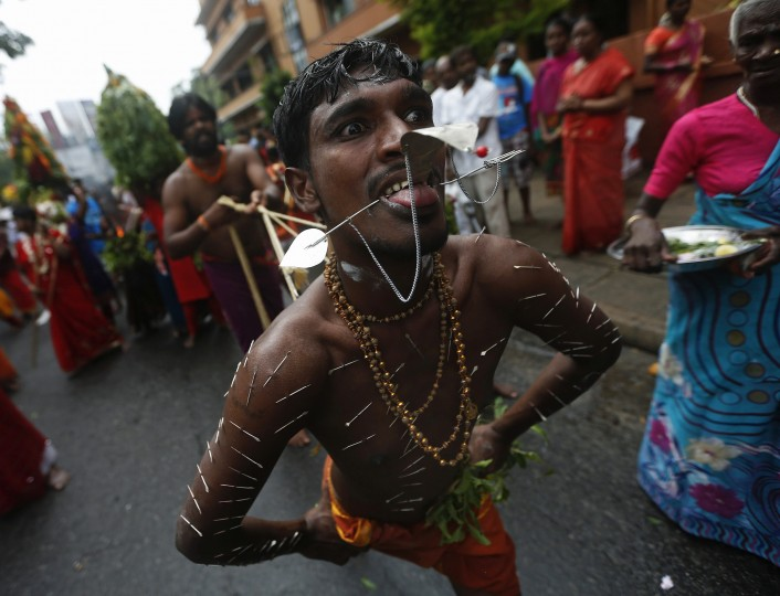 A devotee takes part during in the annual Chariot festival of the Sri Mayurapathy Paththirakaali temple in Colombo. The chariot procession starts at the temple and is brought through streets as Hindu devotees follow behind, performing acts of penance or thanksgiving such as piercing hooks through their skin, in order to fulfill their vows to the Hindu gods. (Dinuka Liyanawatte/Reuters)
