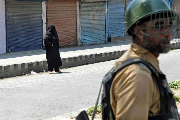 A Kashmiri burqa-clad woman stands as an Indian paramilitary soldier stands guard during restrictions in downtown Srinagar. Chairman of the hardline faction of All Parties Hurriyat (Freedom) Conference, Syed Ali Geelani called for a one-day shutdown to protest against the start of the Kouser Nag yatra (a Hindu pilgrimage) in an ecologically fragile destination in the southern part of Kashmir, although the government has denied giving permission for conducting any such pilgrimage. Senior separatist leaders, including Mirwaiz Umar farooq, Syed Ali Geelani and Shabir Shah have been placed under house arrest. (RoufBhat/AFP-Getty Images)