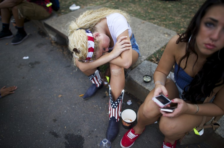 A woman wearing an outfit with the U.S. flag design sleeps on a curb at the Made in America festival in Philadelphia. The two day music festival is organized by Jay-Z and will have a twin concert in Los Angeles. (Mark Makela/Reuters)