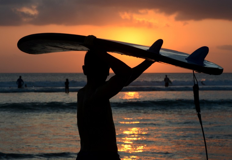 A Balinese surfer carries a surfboard as sunset along Kuta beach on the Indonesian resort island of Bali. Bali is the largest tourist destination in the country and is renowned for its highly developed arts, including traditional and modern dance, sculpture, painting, leather, metalworking, and music. Since the late 20th century, the province has had a rise in tourism. (Sonny Tumbelaka/AFP-Getty Images)