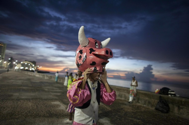 A reveller removes his mask before performing at a carnival parade in Havana. (Alexandre Meneghini/Reuters)