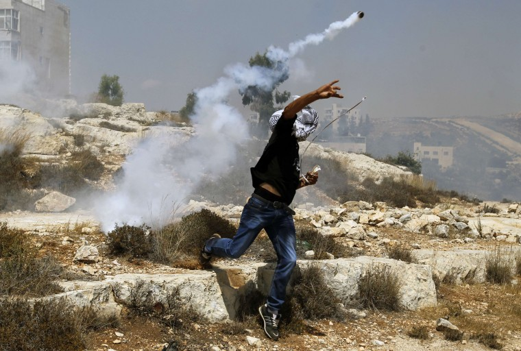 A Palestinian throws back a tear gas canister towards Israeli security forces during clashes following the funeral of 19-year-old Udai Nafez in the West Bank village of Rafat. Udai died the day before after he was shot in the chest in a clash with Israeli forces in Saffa, a village west of Ramallah. (Abbas Momani/AFP-Getty Images)