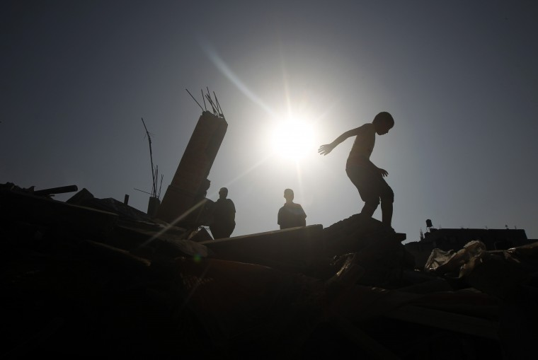 Palestinians inspect the wreckage of a building following an Israeli strike, in Rafah, in the southern Gaza Strip. A fresh wave of violence killed dozens in Gaza after the collapse of a UN and US backed ceasefire, officials said, as Hamas denied it kidnapped an Israeli soldier. (Said Khatib /AFP-Getty Images)