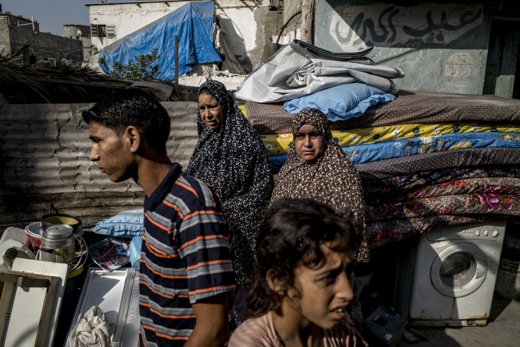 A group of Palestinians stand near salvaged items from their destroyed home at the al-Shati refugee beach camp in Gaza City. A fresh wave of violence killed dozens in Gaza after the collapse of a UN and US backed ceasefire, officials said, as Hamas denied it kidnapped an Israeli soldier. (Marco Longari/AFP-Getty Images)