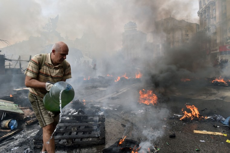 A man extinguishes a fire after Maidan self-defence burned a barricade during clashes with residents of Kiev as thousands of the residents came to remove barricades and tents from the city's central Independence Square, also known as Maidan, and free Khreshchatyk Street for the traffic. A few hundred Maidan activists still live in the tent camp set in the centre of the city that upsets the vast majority of the local residents as the self-defence activists transformed the iconic place into a hotbed of crime, drunkenness and instability. The Kievites assert that the present inhabitants of the current Maidan discredited the very concept of Maidan and call them Alco-Maidan. . (Sergei Supinsky/AFP-Getty Images)