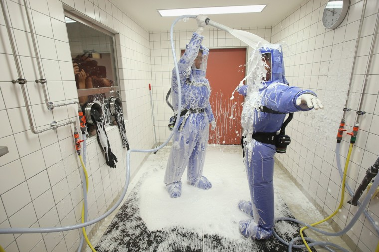 A doctor for tropical medicine and a nurse demonstrate the decontamination procedure as part of ebola treatment at Station 59 at Charite hospital on August 11, 2014 in Berlin, Germany. The specialized quarantine unit at Station 59 is among a handful of facilities in Germany nationwide that are capable of handling ebola cases. According to media reports a German medical student currently in Ruanda is showing signs of the disease, though should he in fact have ebola it is so far unclear whether he would be flown to Germany for treatment. The disease has so far claimed over 1,000 lives in western Africa in recent weeks. (Photo by Sean Gallup/Getty Images)