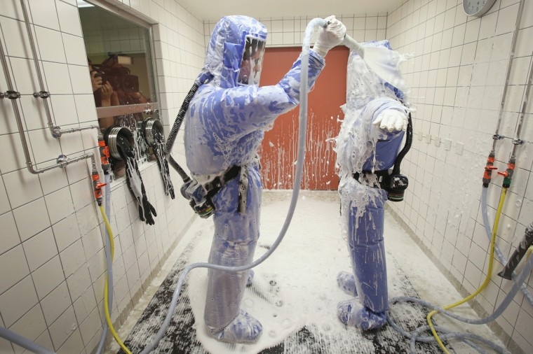 A nurse and a doctor for tropical medicine wearing isolation suits demonstrate the decontamination procedure as part of ebola treatment capability at Station 59 at Charite hospital on August 11, 2014 in Berlin, Germany. The specialized quarantine unit at Station 59 is among a handful of facilities in Germany nationwide that are capable of handling ebola cases. According to media reports a German medical student currently in Ruanda is showing signs of the disease, though should he in fact have ebola it is so far unclear whether he would be flown to Germany for treatment. The disease has so far claimed over 1,000 lives in western Africa in recent weeks. (Photo by Sean Gallup/Getty Images)