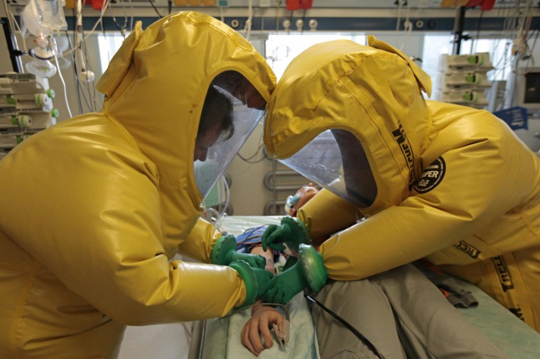 Czech military personnel wearing protective gear take part in a drill with a dummy in the Biological Defence Centre, a specialised medical institution ensuring complete biological defence, in the village of Techonin August 11, 2014. The Biological Defence Department is involved in the NATO biological defence system and is equipped for treatment of possible Ebola virus patients. (David W Cerny/Reuters)