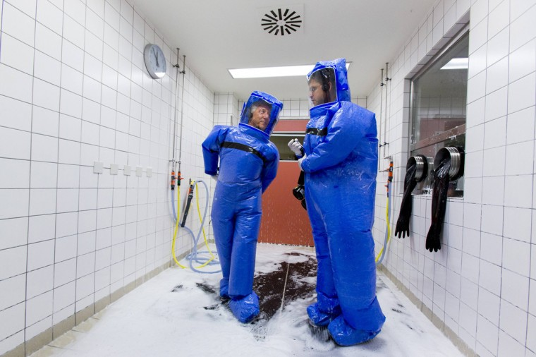 "Doctor for tropical medicine Florian Steiner (R) and ward physician Thomas Klotzkowski stand in a disinfection chamber after cleaning their protective suits at the quarantine station for patients with infectious diseases at the Charite hospital in Berlin August 11, 2014. The isolation ward at the Charite is one of several centres in Germany equipped to treat patients suffering from ebola and other highly infectious diseases, the clinic's doctor for tropical medicine Florian Steiner said. Ebola is one of the deadliest diseases known to humanity. It has no proven cure and there is no vaccine to prevent infection. The most effective treatment involves alleviating symptoms that include fever, vomiting and diarrhoea. The rigorous use of quarantine is needed to prevent its spread, as well as high standards of hygiene for anyone who might come into contact with the disease. The sign reads: ""Do not Enter. Infectious Diseases. No Trespassing!"" . (Thomas Peter/Reuters)"