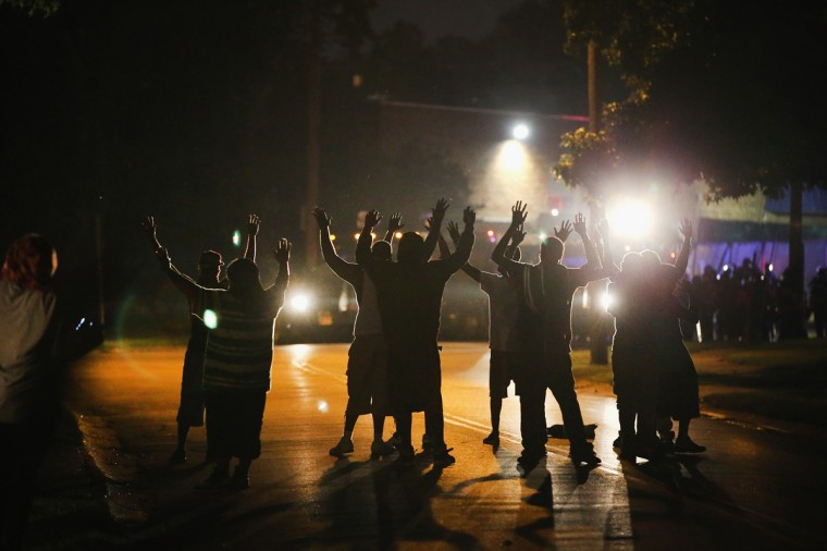 With their hands raised, residents gather at a police line as the neighborhood is locked down following skirmishes on August 11, 2014 in Ferguson, Missouri. Police responded with tear gas as residents and their supporters protested the shooting by police of an unarmed black teenager named Michael Brown who was killed Saturday in this suburban St. Louis community. Yesterday 32 arrests were made after protests turned into rioting and looting in Ferguson. (Photo by Scott Olson/Getty Images)