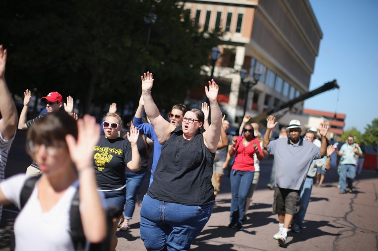 "Demonstrators raise their hands and chant ""hands up, don't shoot"" during a protest over the killing of Michael Brown on August 12, 2014 in Clayton, Missouri. Some reports state that Brown hand his hands in the air when he was shot and killed by a police officer on Saturday in suburban Ferguson, Missouri. Two days of unrest including rioting and looting have followed the shooting in Ferguson. Browns parents have publicly asked for order. (Photo by Scott Olson/Getty Images)"