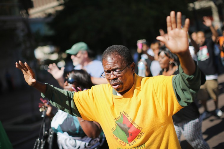 """Demonstrators raise their hands and chant """"hands up, don't shoot"""" during a protest over the killing of Michael Brown on August 12, 2014 in Clayton, Missouri. Some reports state that Brown hand his hands in the air when he was shot and killed by a police officer on Saturday in suburban Ferguson, Missouri. Two days of unrest including rioting and looting have followed the shooting in Ferguson. Browns parents have publicly asked for order. (Photo by Scott Olson/Getty Images)"""