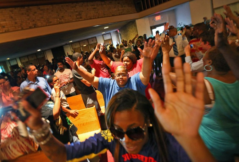 "A group of young protestors at the Greater St. Mark Missionary Baptist Church enter the church chanting, ""Hands up, don't shoot"" on Tuesday, Aug. 12, 2014, in Dellwood, Mo. The gathering at the church was in response to the police shooting of 18-year-old Michael Brown on Saturday. (Chris Lee/St. Louis Post-Dispatch/MCT)"