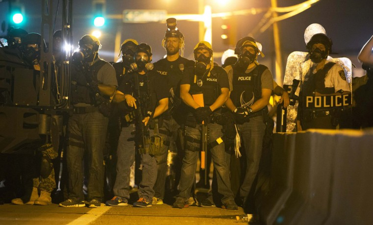 Police officers keep watch while demonstrators (not pictured) protest the death of black teenager Michael Brown in Ferguson, Missouri August 12, 2014. Police said Brown, 18, was shot in a struggle with a gun in a police car but have not said why Brown was in the car. At least one shot was fired during the struggle and then the officer fired more shots before leaving the car, police said. But a witness to the shooting interviewed on local media has said that Brown had been putting his hands up to surrender when he was killed. The FBI has opened a civil rights investigation into the racially charged case and St. Louis County also is investigating. (Mario Anzuoni/Reuters)
