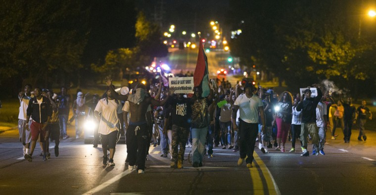 Demonstrators march in the street while protesting the shooting death of black teenager Michael Brown in Ferguson, Missouri August 12, 2014. Police said Brown, 18, was shot in a struggle with a gun in a police car but have not said why Brown was in the car. At least one shot was fired during the struggle and then the officer fired more shots before leaving the car, police said. But a witness to the shooting interviewed on local media has said that Brown had been putting his hands up to surrender when he was killed. The FBI has opened a civil rights investigation into the racially charged case and St. Louis County also is investigating. (Mario Anzuoni/Reuters)