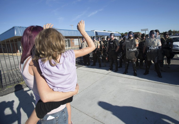 A mother and daughter raise their hands in front of riot police while protesting the shooting death of teenager Michael Brown, in Ferguson, Missouri August 13, 2014. Police in Ferguson fired several rounds of tear gas to disperse protesters late on Wednesday, on the fourth night of demonstrations over the fatal shooting last weekend of an unarmed black teenager Brown, 18, by a police officer on Saturday after what police said was a struggle with a gun in a police car. A witness in the case told local media that Brown had raised his arms to police to show that he was unarmed before being killed. (Mario Anzuoni/Reuters)