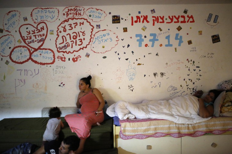 """Israelis are seen in a bomb shelter in the Israeli southern city of Ashkelon July 31, 2014. Israel declared a Gaza ceasefire over on Friday, saying Hamas militants breached the truce soon after it came in effect and apparently captured an Israeli officer while killing two other soldiers. The 72-hour break announced by U.S. Secretary of State John Kerry and U.N. Secretary-General Ban Ki-moon was the most ambitious attempt so far to end more than three weeks of fighting, and followed mounting international alarm over a rising Palestinian civilian death toll. The writings on the wall in Hebrew spells out the names of families and the names of the Israeli operations in the Gaza Strip """"Operation Protective Edge, Operation Pillar Defense, Operation Cast Lead"""". Picture taken July 31, 2014. (Amir Cohen/Reutrs)"""