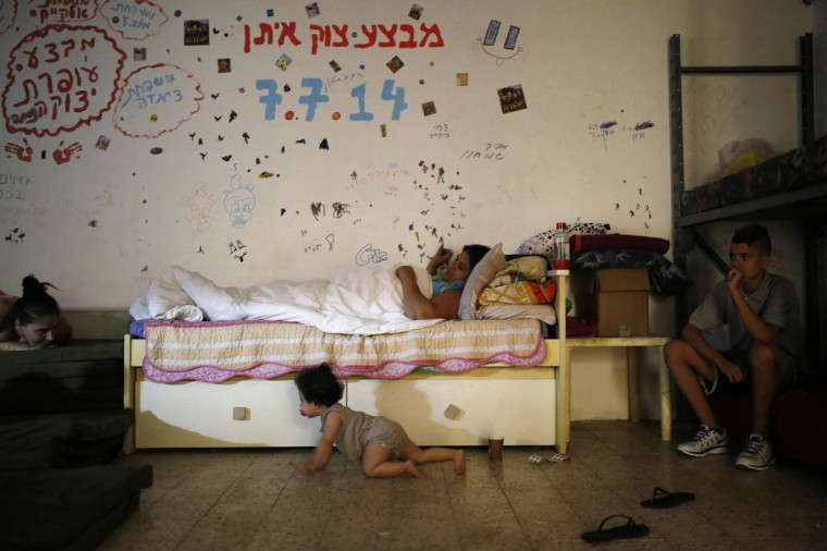 """Israelis are seen in a bomb shelter in the Israeli southern city of Ashkelon July 31, 2014. Israel declared a Gaza ceasefire over on Friday, saying Hamas militants breached the truce soon after it came in effect and apparently captured an Israeli officer while killing two other soldiers. The 72-hour break announced by U.S. Secretary of State John Kerry and U.N. Secretary-General Ban Ki-moon was the most ambitious attempt so far to end more than three weeks of fighting, and followed mounting international alarm over a rising Palestinian civilian death toll. The writings on the wall in Hebrew spells out the names of families and the names of the Israeli operations in the Gaza Strip """"Operation Protective Edge, Operation, Operation Cast Lead"""". Picture taken July 31, 2014. (Amir Cohen/Reutrs)"""