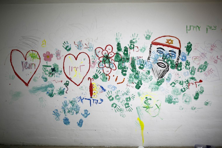"""A wall decorated with paintings by children are seen in a bomb shelter in the Israeli southern city of Ashkelon July 31, 2014. Israel declared a Gaza ceasefire over on Friday, saying Hamas militants breached the truce soon after it came in effect and apparently captured an Israeli officer while killing two other soldiers. The 72-hour break announced by U.S. Secretary of State John Kerry and U.N. Secretary-General Ban Ki-moon was the most ambitious attempt so far to end more than three weeks of fighting, and followed mounting international alarm over a rising Palestinian civilian death toll. The words in Hebrew read, """"Protective Edge"""". Picture taken July 31, 2014. (Amir Cohen/Reuters)"""