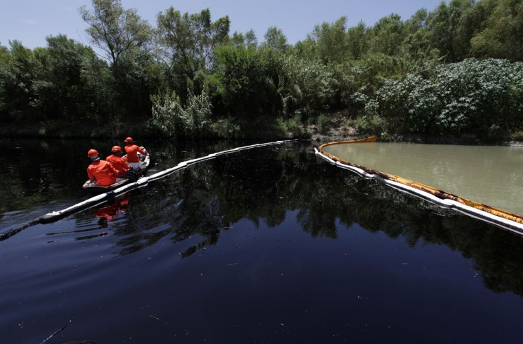 Workers navigate near containment booms while trying to clean the river San Juan from leaked oil in Cadereyta August 22, 2014. (REUTERS/Daniel Becerril)