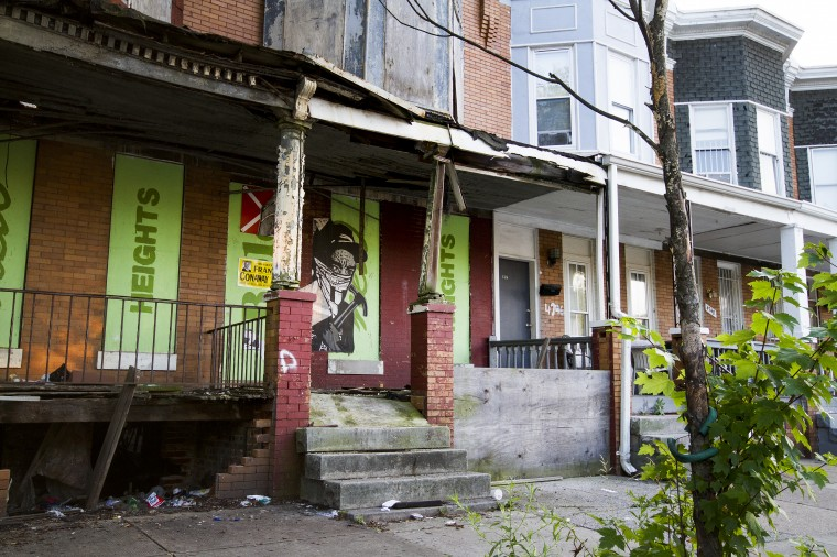 Vacant rowhomes are plastered with hopeful campaign slogans from the Park Heights Renaissance firm and artwork in the 4700 block of Park Heights Avenue. (Kalani Gordon/The Baltimore Sun/August 2014)