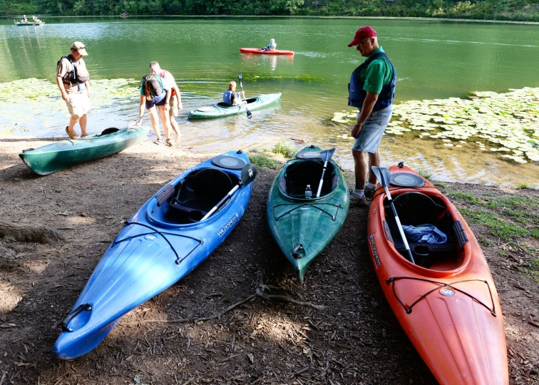 Bill Matejka, right, of Abingdon, looks at his kayak choices before embarking on a sunset nature tour of the Piney Run Reservoir in Sykesville, Saturday, Aug. 16, 2014. (Jon Sham/BSMG)