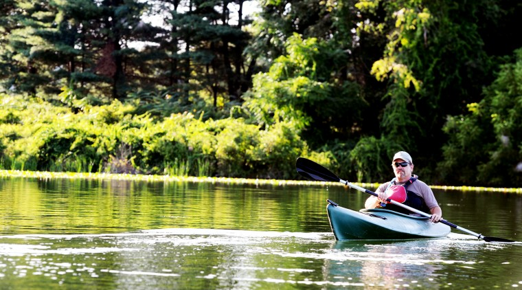 Joel Beckwith, a naturalist who leads kayaking tours for the Piney Run Nature Center in Sykesville, turns his kayak around to wait for his participants, Saturday, Aug. 16, 2014. (Jon Sham/BSMG)