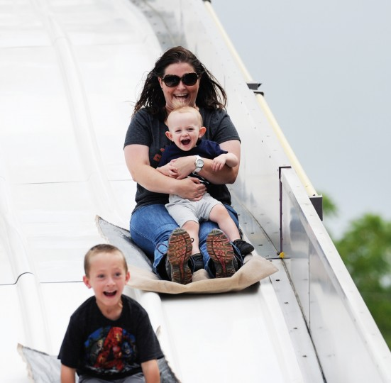 Kristen Seabolt, of Westminster, goes down the burlap sack slide with her sons, Landon, 18 months, on her lap, and Vance, 5, at the Howard County Fair in West Friendship on Sunday, Aug. 3, 2014. (Jon Sham/BSMG)