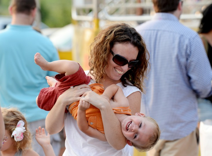 Rebecca Fecteau, of Mt. Airy, plays with her 18-month-old song, Jacob Fecteau, while they wait in line for a ride at the Howard County Fair in West Friendship, Thursday, Aug. 7, 2014. (Jon Sham/BSMG)