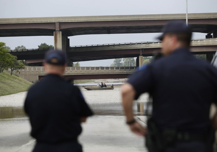 Michigan State Police Officers watches as other officers check a flooded underpass by boat along Interstate-75 and Interstate 696 for vehicles and victims August 12, 2014 in Hazel Park, Michigan. Sever rain from yesterday's storm flooded local streets, highways, and homes in the Detroit Metropolitan area experiencing the worst flash flooding in decades. (Photo by Joshua Lott/Getty Images)