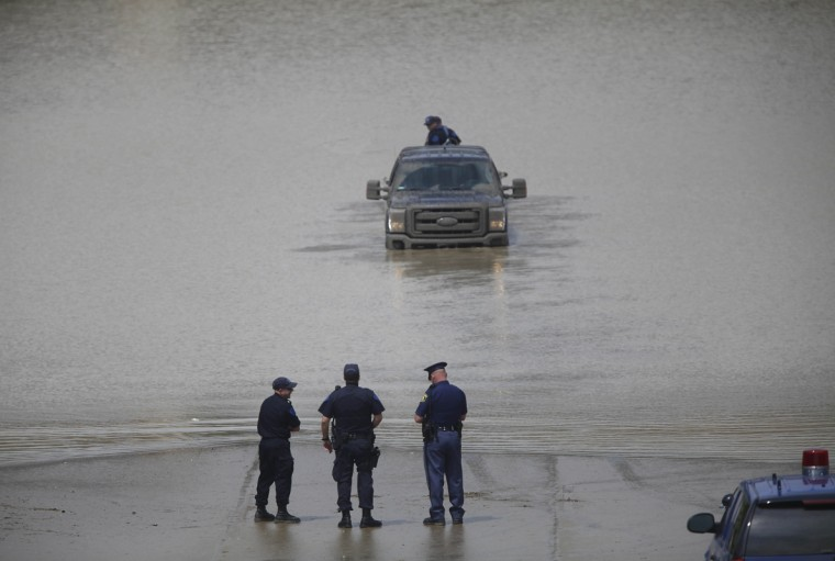 Michigan State Police Officers check a flooded underpass along Interstate-75 and Interstate 696 for vehicles and victims August 12, 2014 in Hazel Park, Michigan. Sever rain from yesterday's storm flooded local streets, highways, and homes in the Detroit Metropolitan area experiencing the worst flash flooding in decades. (Photo by Joshua Lott/Getty Images)