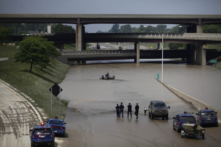Michigan State Police Officers check a flooded underpass by boat along Interstate-75 and Interstate 696 for vehicles and victims August 12, 2014 in Hazel Park, Michigan. Sever rain from yesterday's storm flooded local streets, highways, and homes in the Detroit Metropolitan area experiencing the worst flash flooding in decades. (Photo by Joshua Lott/Getty Images)
