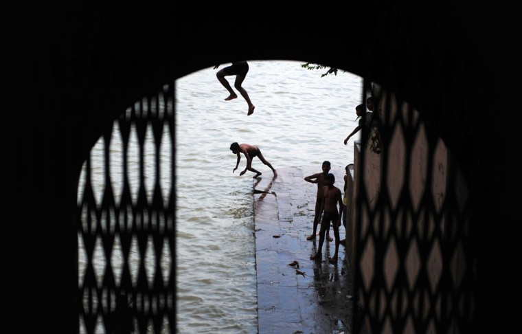 Indian youth jump into the flooded river Ganga as water levels of the River Ganga increase in Allahabad on August 11, 2014. Heavy rain in several areas of north India has caused rivers to reach the danger mark and flooding has occurred in various places. (Sanjay Kanojia/AFP/Getty Images)