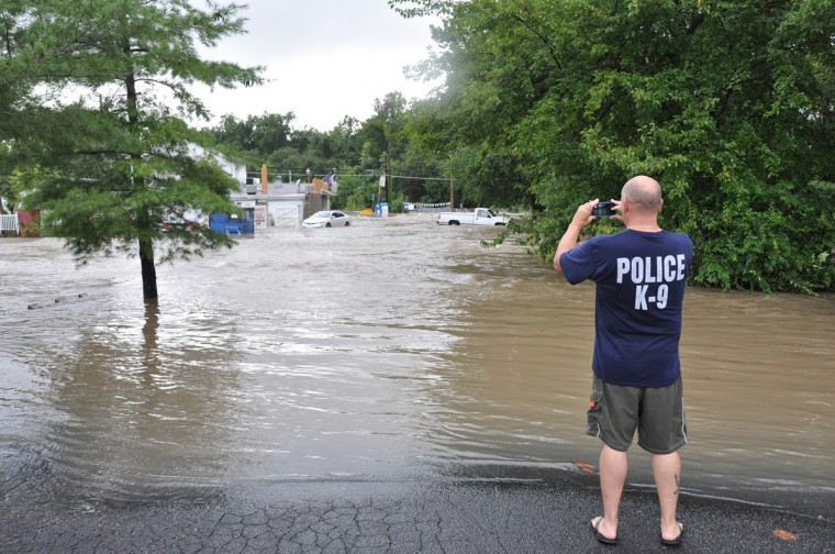 A bystander takes pictures of Sawmill Creek in Glen Burnie, which overran its banks on Tuesday afternoon and flooded nearby businesses. (Pamela Wood/Baltimore Sun staff)