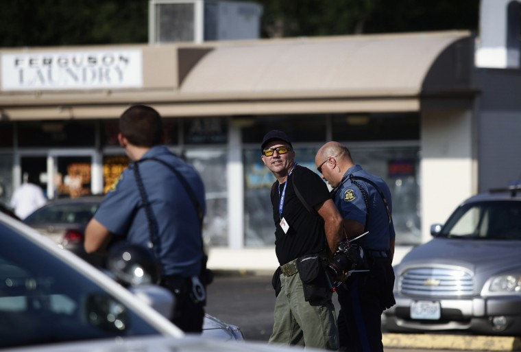 Getty Images photographer (C) is arrested by a highway patrol officer during a protest for the shooting death of Michael Brown, in Ferguson, Missouri August 18, 2014. He was arrested because police required media to be within certain areas, media quoted another journalist as saying. Missouri Governor Jay Nixon lifted the curfew for the St. Louis suburb of Ferguson on Monday and began deploying National Guard troops to help quell days of rioting and looting spurred by the fatal shooting of the black unarmed teenager by a white policeman. (Joshua Lott/Reuters)