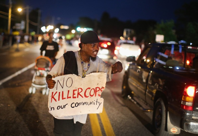 A demonstrator holds a sign along West Florissant Avenue to protest the shooting death of Michael Brown on August 14, 2014 in Ferguson, Missouri. Violent protests have erupted along West Florissant in Ferguson each of the last four nights as demonstrators express outrage over the shooting death of Michael Brown by a Ferguson police officer on August 9. (Photo by Scott Olson/Getty Images)
