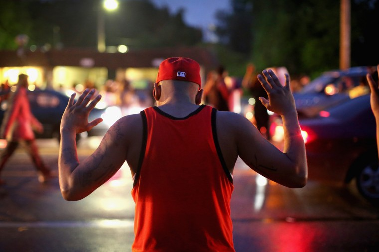 """Demonstrators gather along West Florissant Avenue to protest the shooting of Michael Brown on August 15, 2014 in Ferguson, Missouri. Brown was shot and killed by a Ferguson police officer on August 9. Protestors raise their hands and chant """"Hands up, don't shoot"""" as a rally cry to draw attention to reports that stated Brown's hands were raised when he was shot. Tonight demonstration again ended with protestors clashing with police followed by more looting. (Photo by Scott Olson/Getty Images)"""