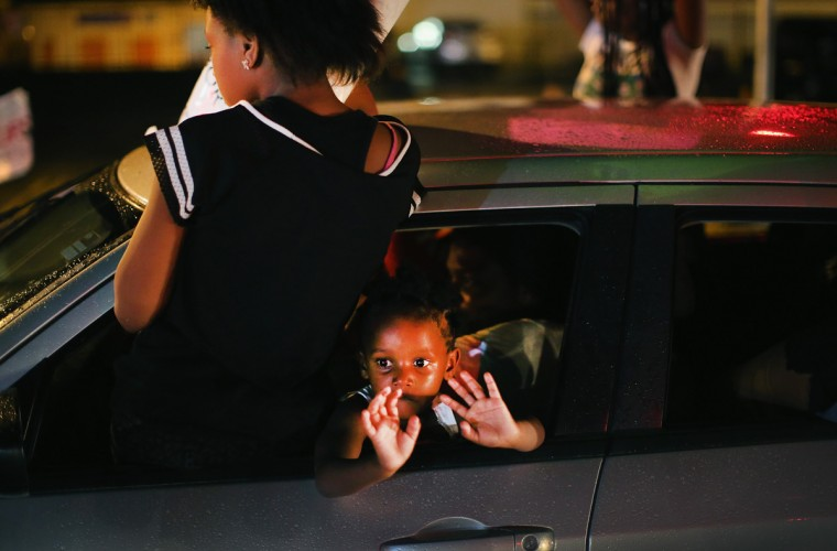 """A young child looks out from a car as demonstrators drive down West Florissant Avenue protesting the shooting and death of Michael Brown on August 15, 2014 in Ferguson, Missouri. Brown was shot and killed by a Ferguson police officer on August 9. Protestors raise their hands and chant """"Hands up, don't shoot"""" as a rally cry to draw attention to reports that stated Brown's hands were raised when he was shot. Tonight demonstration again ended with protestors clashing with police followed by more looting. (Photo by Scott Olson/Getty Images)"""