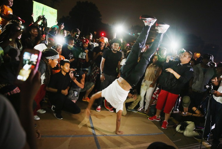 A group of young men breakdance for demonstrators gathered along West Florissant Avenue to protest the shooting of Michael Brown on August 15, 2014 in Ferguson, Missouri. Brown was shot and killed by a Ferguson police officer on August 9. Tonight's demonstration again ended with protestors clashing with police followed by more looting. (Photo by Scott Olson/Getty Images)