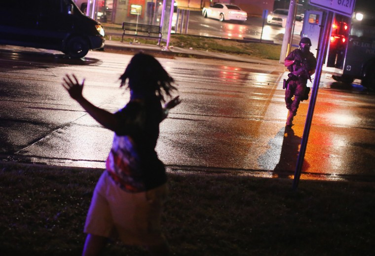 A Police officer confronts a demonstrators during a protest over the shooting death of Michael Williams on August 15, 2014 in Ferguson, Missouri. Police shot pepper spray, smoke, gas and flash grenades at protestors before retreating. Several businesses were looted as the county police sat nearby with armored personnel carriers (APC). Violent outbreaks have taken place in Ferguson since the shooting death of Brown by a Ferguson police officer on August 9. (Photo by Scott Olson/Getty Images)