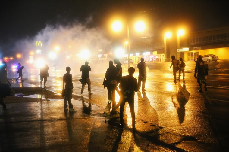 Police fire tear gas at demonstrators protesting the shooting of Michael Brown after they refused to honor the midnight curfew on August 17, 2014 in Ferguson, Missouri. The curfew was imposed on Saturday in an attempt to reign in the violence that has erupted nearly every night in the suburban St. Louis town since the shooting death of teenager Michael Brown by a Ferguson police officer on August 9. (Photo by Scott Olson/Getty Images)