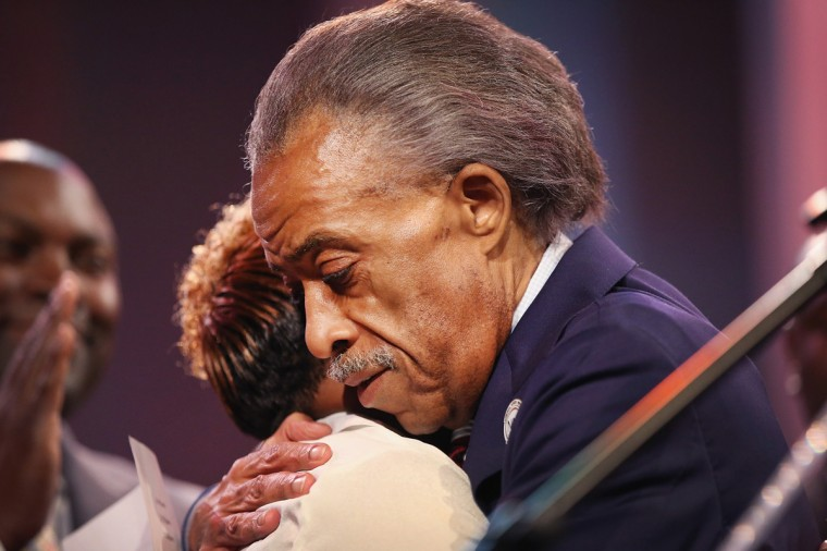 Rev Al Sharpton hugs Lesley McSpadden, the mother of slain teenager Michael Brown, during a rally at Greater Grace Church on August 17, 2014 in Ferguson, Missouri. Brown was shot and killed by a Ferguson police officer on August 9. Despite the Brown family's continued call for peaceful demonstrations, violent protests have erupted nearly every night in Ferguson since his death. (Photo by Scott Olson/Getty Images)