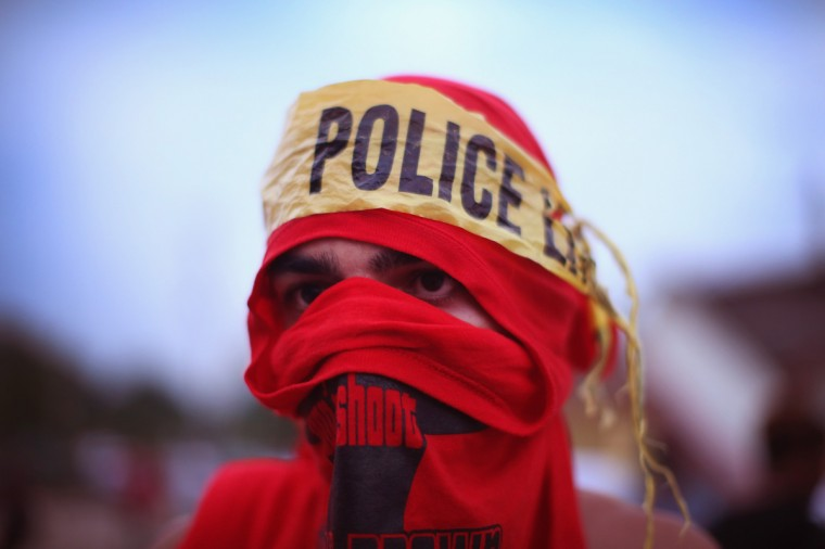 A demonstrator wears a makeshift headscarf with police tape around it as he takes part in a protest at the killing of teenager Michael Brown on August 17, 2014 in Ferguson, Missouri. Despite the Brown family's continued call for peaceful demonstrations, violent protests have erupted nearly every night in Ferguson since his death. (Photo by Scott Olson/Getty Images)