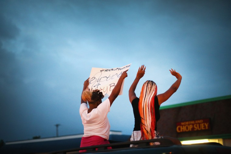 Demonstrators raise their arms during a protest against the killing of teenager Michael Brown on August 17, 2014 in Ferguson, Missouri. Despite the Brown family's continued call for peaceful demonstrations, violent protests have erupted nearly every night in Ferguson since his death. (Photo by Scott Olson/Getty Images)