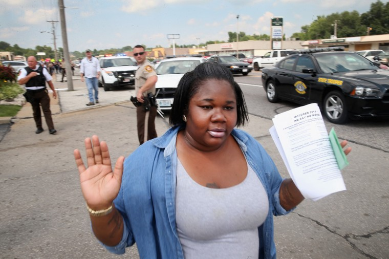 A woman raises her hands as she walks by police shortly after they arrested a demonstrator protesting the killing of teenager Michael Brown on August 18, 2014 in Ferguson, Missouri. After a protest yesterday ended with a barrage of tear gas and gunfire, Missouri Governor Jay Nixon activated the national guard to help with security. Brown was shot and killed by a Ferguson police officer on August 9. Despite the Brown family's continued call for peaceful demonstrations, violent protests have erupted nearly every night in Ferguson since his death. (Photo by Scott Olson/Getty Images)