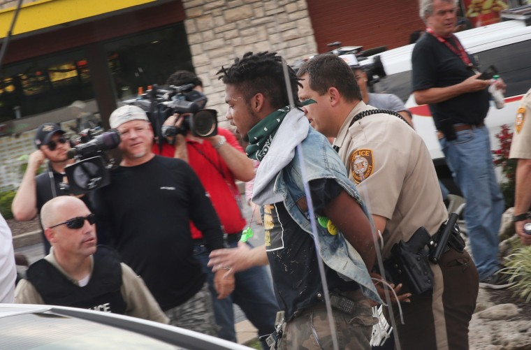 Police arrest a demonstrator protesting the killing of teenager Michael Brown on August 18, 2014 in Ferguson, Missouri. After a protest yesterday ended with a barrage of tear gas and gunfire, Missouri Governor Jay Nixon activated the national guard to help with security. Brown was shot and killed by a Ferguson police officer on August 9. Despite the Brown family's continued call for peaceful demonstrations, violent protests have erupted nearly every night in Ferguson since his death. (Photo by Scott Olson/Getty Images)