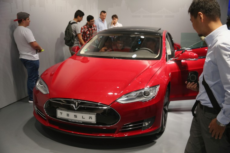 Visitors look at a Tesla Model S electric car at the Panasonic stand at the 2014 IFA home electronics and appliances trade fair in Berlin, Germany. IFA is the world's biggest fair of its kind and is open to the public through September 10. (Sean Gallup/Getty Images)