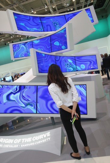 A stand hostess stands next to a display of Ultra HD curved television monitors at the Samsung stand at the 2014 IFA home electronics and appliances trade fair on September 5, 2014 in Berlin, Germany. IFA is the world's biggest fair of its kind and is open to the public through September 10. (Sean Gallup/Getty Images)