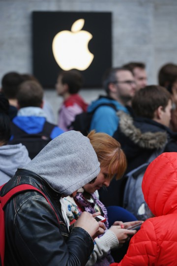 People type on older model Apple iPhones as they wait to enter the Apple Store at 8am on the first day of sales of the new Apple iPhone 6 in Germany on September 19, 2014 in Berlin, Germany. Hundreds of people had waited in a line that went around the block through the night in order to be among the first people to buy the new smartphone, which comes in two versions: the Apple iPhone 6 and the somewhat larger Apple iPhone 6 Plus. Sean Gallup/Getty Images