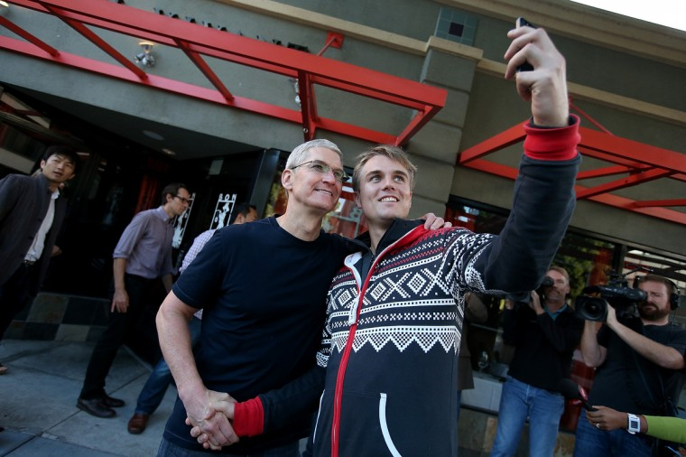 Apple CEO Tim Cook (L) takes a selfie photo with a man waiting in line to buy the new iPhone 6 at an Apple Store on September 19, 2014 in Palo Alto, California. Justin Sullivan/Getty Images